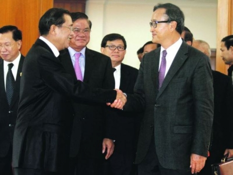 Prime Minister Hun Sen (left) and CNRP leader Sam Rainsy perform for the cameras.  (Source: Khmer Times)