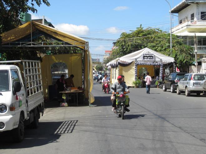 On a highly trafficked street, the tent on the left is for for food preparation, while the one on the right is for remembering the dead.  Please note the white attire.