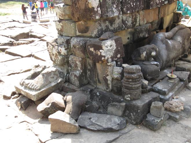 Broken sculpture awaits restaurant outside the Bayon temple.