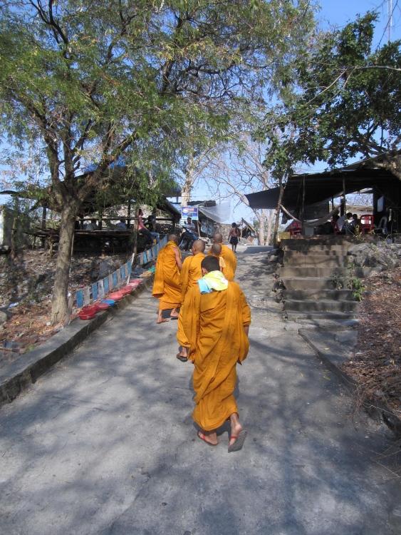Monks near the peak where Wat Sampeau glistens.