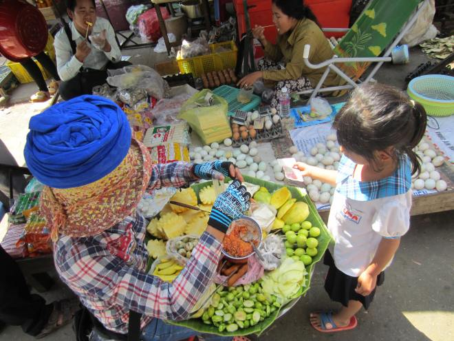 A boy makes the inevitable hard choice of a treat in the Battambang's wholesale food market.