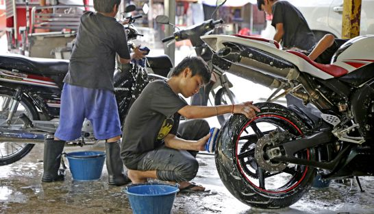 Lots of young people work at washing vehicles, including the boy wearing shorts too big for him.