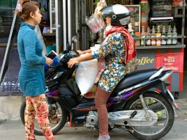 This woman likely is carrying home what may be a bag of rice.