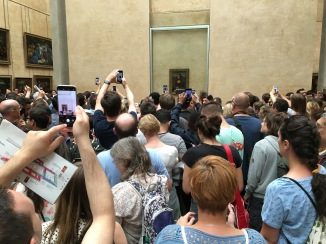 Visitors contemplating Mona Lisa at the Louvre, where hordes of visitors viewed all the art through their smartphones.